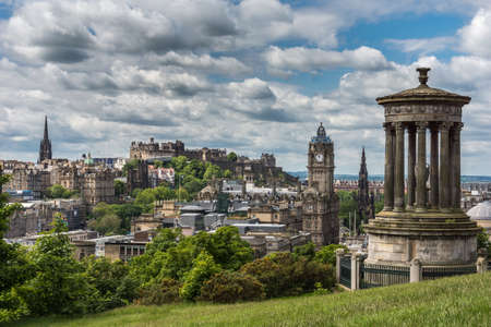 Edinburgh, Scotland, UK - June 13, 2012: Donald Stewart monument on Calton Hill with old town, castle, New College, Lloyds Banking group, Balmoral Clock tower, Scott Monument under heavy cloudscape.