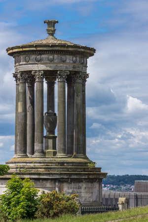 Edinburgh, Scotland, UK - June 13, 2012: Closeup of brown stone Donald Stewart Monument on Calton Hill. All under heavy cloudscape. Editorial