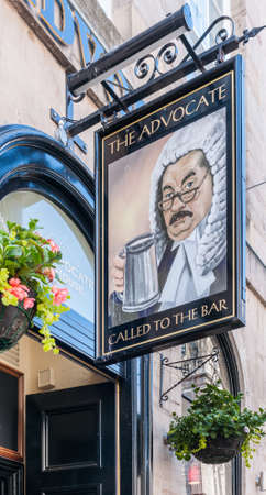 Edinburgh, Scotland, UK - June 13, 2012: Closeup of Welcome board at entrance to The Advocate restaurant and bar features serious head of judge holding a pint of beer. Facade with hanging flower pots. Éditoriale
