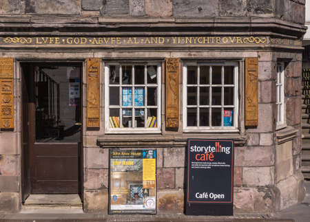 Edinburgh, Scotland, UK - June 13, 2012: Pub and restaurant street level of John Knox House, a protestant reformer. Golden slogan, books and two advertisements boards.