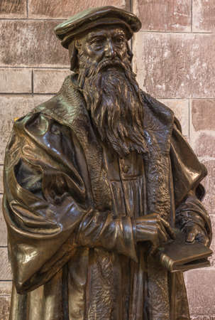 Edinburgh, Scotland, UK - June 13, 2012; Closeup of bronze statue of bearded John Knox upper body holding book in his hand, at St Giles Cathedral.