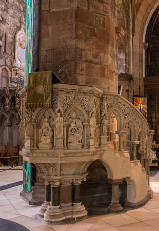 Edinburgh, Scotland, UK - June 13, 2012; St Giles Cathedral. Monumental deacorated stone pulpit against massive pillar.