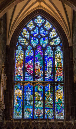 Edinburgh, Scotland, UK - June 13, 2012; St Giles Cathedral. Stained window in dark niche features scenery of boats in stormy weather and imminent peril. Christianity to the rescue.
