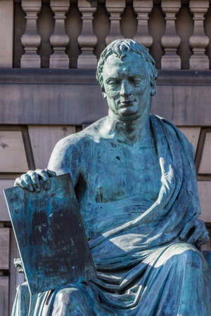 Edinburgh, Scotland, UK - June 13, 2012; Closeup of David Hume green bronze statue outside Court House on Lawnmarket. Beige stone wall as background. 報道画像