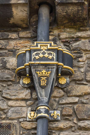 Edinburgh, Scotland, UK - June 14, 2012: Closeup of golden Royal symbols on hopper water collection box on top of downpipe from gutter at Castle.