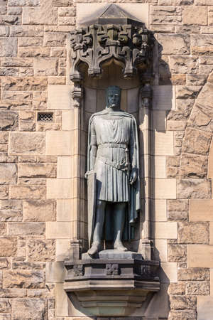 Edinburgh, Scotland, UK - June 14, 2012: Closeup of bronze Robert the Bruce statue on brown facade of Castle Gatehouse.