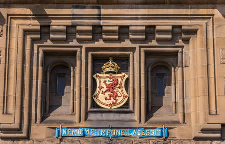 Edinburgh, Scotland, UK - June 14, 2012: Closeup of Scottish Royal National coat of arms with crown and Nemo Me Impune Lacessit slogan set in brown wall of Castle Gatehouse.