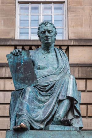 Edinburgh, Scotland, UK - June 14, 2012; Closeup of David Hume green bronze statue outside Court House on Lawnmarket. Beige stone wall as background.