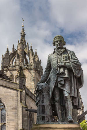 Edinburgh, Scotland, UK - June 14, 2012: Adam Smith bronze statue on market square in front of brown stone Saint Gilles Cathedral under blue sky with clouds.