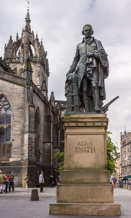 Edinburgh, Scotland, UK - June 14, 2012: Adam Smith bronze statue on market square in front of brown stone Saint Gilles Cathedral under blue sky with clouds. Street scene with people.