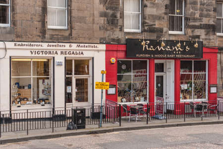 Edinburgh, Scotland, UK - June 14, 2012: Beige facade jewelry store and red facade Kurdish Middel Eastern restaurant on Royal Mile, as street level businesses in historic brown stone buildings.