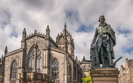 Edinburgh, Scotland, UK - June 14, 2012: Adam Smith bronze statue on market square in front of brown stone Saint Gilles Cathedral crown tower under gray silver sky with blue patches. Mercat Cross pillar.