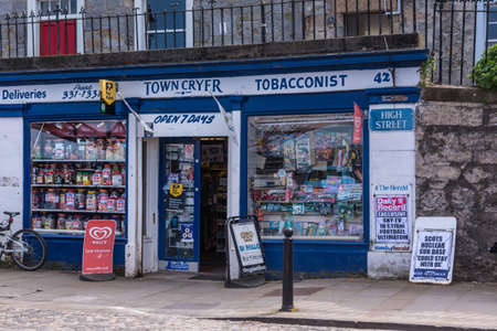 Queensferry, Scotland, UK - June 14, 2012: Blue and white painted facade of Town Cryer Tobacconist on High Street. As also news stand, plenty of advertisement for printed material. Archivio Fotografico - 118092942
