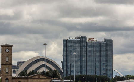 Glasgow, Scotland, UK - June 17, 2012: Crown Plaza hotel and SEC Armadillo with clocktower and part of The Clyde Arc under heavy cloudscape.
