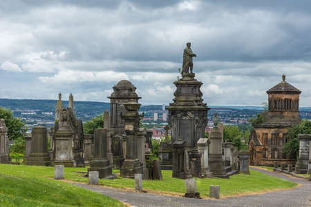 Glasgow, Scotland, UK - June 17, 2012: Necropolis. Collection of molded grave memorial statues and tombstones on top of hill, shows the wider city and skyline on horizon, cloudscape.
