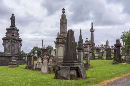Glasgow, Scotland, UK - June 17, 2012: Necropolis. Group of tall and short memorial brown molded stone monuments with John Knox obelisk under heavy cloudscape. Green grass Redactioneel