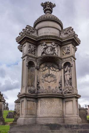 Glasgow, Scotland, UK - June 17, 2012: Necropolis. Brown stone monumental mausoleum of John Henry Alexander, with statues against heavy sky. Green grass.