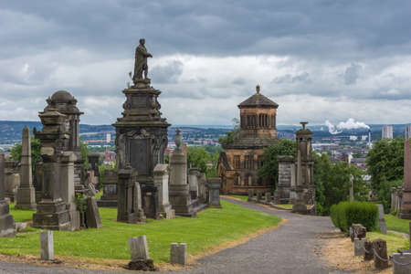 Glasgow, Scotland, UK - June 17, 2012: Necropolis. Collection of molded grave memorial statue of William McGavin and tombstones on top of hill, shows the wider city and skyline on horizon, cloudscape. Editorial
