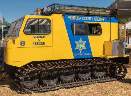 Fillmore, California, USA - September 30, 2018: closeup of Yellow and blue search and rescue vehicle with Caterpillar or Tank track belonging to Ventura County Sheriff Offices. Blue sky, yellow straw.