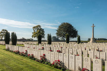 Proven, Flanders, Belgium - September 15, 2018: Overview of Mendinghem British war cemetery under blue morning sky. Green lawn, beige tomb stones and red roses with dark green trees sprinkled.
