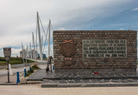 Dunkerque, France - September 16, 2018: Brown stone war memorial commemorating the Battle for Dunkirk in world war 2 near the beach. Pedestrial suspension bridge under blue-white sky.