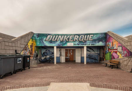 Dunkerque, France - September 16, 2018: Colorful wall paintings of Public toilet facilities on boardwalk along Dunkirk beach. Brown stone walls. White gray sky. Editorial