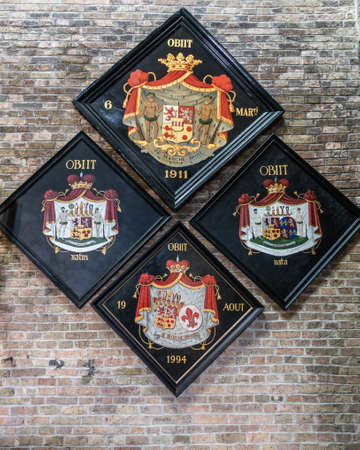 Brugge, Flanders, Belgium - September 19, 2018: Four colorful Family coat of arms on brick wall in Jerusalem Church of Bruges.