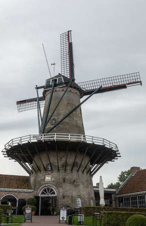 Sluis, Zeeland, Netherlands - September 22, 2018: The windmill of Sluis, gray brick structure with wooden circular walkway against silver sky is a restaurant, tearoom and pub. Some green vegetation.