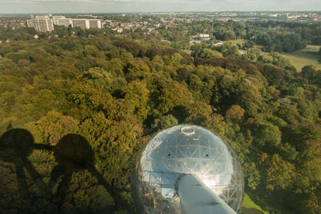 Brussels, Belgium - September 25, 2018: One shining metalic sphere and shadows of others of the Atomium monument. Shot from above with green Laken Park as background.