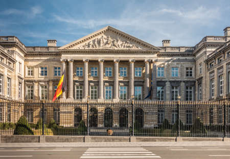 Brussels, Belgium - September 26, 2018: Facade of Belgian Parliament in romanesque style with pillars and fresco triangle, black-gold fence and Belgian and European flag. Front is Wetstraat.
