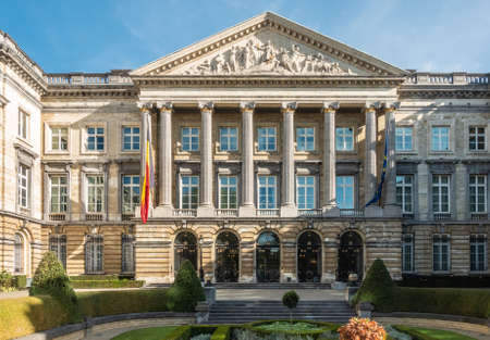Brussels, Belgium - September 26, 2018: Closeup of front Facade of Belgian Parliament in romanesque style with pillars and fresco triangle, and  Belgian and European flag.