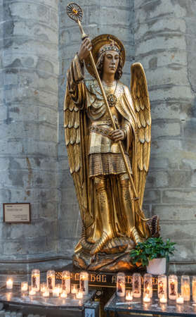 Brussels, Belgium - September 26, 2018: Closeup of Statue of Saint Michael in Cathedral of Saint Michael and Saint Gudula against gray stone wall of pillar. Burning candles up front.