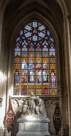 Brussels, Belgium - September 26, 2018: Stained Glass Window of Cathedral of Saint Michael and Saint Gudula. White stone tomb monument in front.