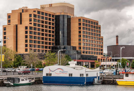 Hobart, Tasmania, Australia - December 13, 2009: Hotel Grand Chancellor combines brown and black in its modern functional architecture. Boats of harbor up front. Gray cloudscape.