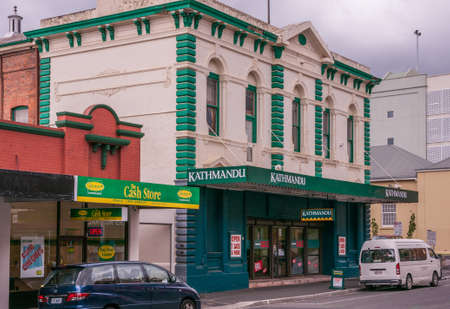 Hobart, Tasmania, Australia - December 14, 2009:  Kathmandu outdoor and camping store in historic merchant house painted green and beige. Street scene with cars and The Cash Store. Editorial