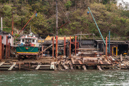 Hong Kong, China  - May 12, 2010: Brown wooded slipways and dry docks to repair and maintain small fishing and other vessels. Green foliage of hill in backdrop. Greenish water. One boat on dock. Editöryel