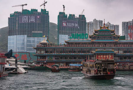 SONY Hong Kong, China  - May 12, 2010: Massive colorful traditional architectural Jumbo Floating Restaurant in harbor. Highrise towers under construction in back. Boat traffic on greenish water.