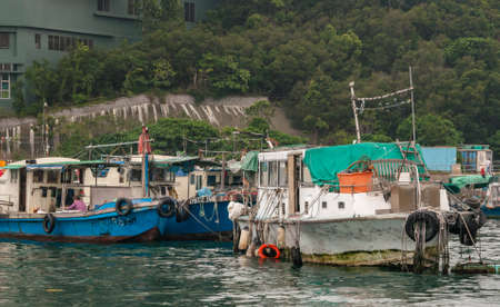 Hong Kong, China  - May 12, 2010: Blue and white old houseboats in harbor. Some might still be used as small fishing vessels. Green hill as backdrop. 報道画像
