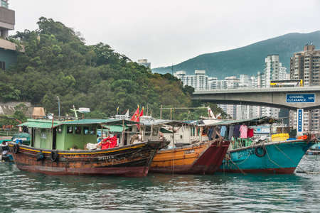 Hong Kong, China  - May 12, 2010: Blue and brown wooden old houseboats in harbor. Some might still be used as small fishing vessels. Green hill, tall highrise buildings and bridge as backdrop.