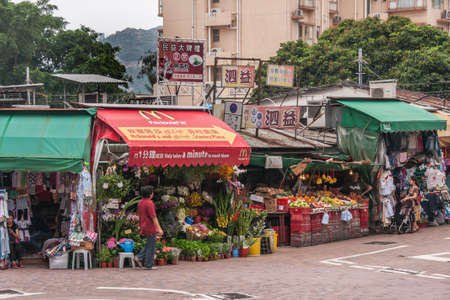 Hong Kong Island, China  - May 12, 2010: Row of market stalls sell clothing, flowers, fruits and vegetables. One booth roof sports advertisement for Mcdonalds burgers. Customers and housing in bac.k. Editorial