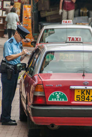 Hong Kong Island, China  - May 12, 2010: A traffic cop in blue writes a red taxi cab up for an infraction near Stanley Market. Faded shops and vendors in back. Archivio Fotografico - 118093590