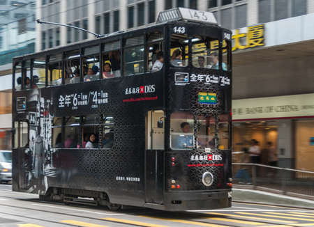 Hong Kong Island, China  - May 14, 2010: Des Voeux Road Central. Black streetcar features advertisement for DBS Bank showing shopping people and figures.  Street scene with  people. Редакционное