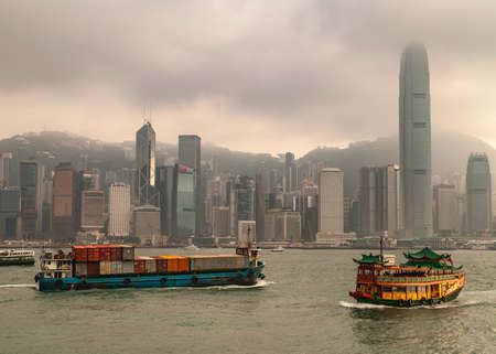 Hong Kong Island, China  - May 12, 2010: Skyline with International Finance Center and more under dark foggy sky,. Container ship and Watertours sampan-style river cruise boat in front on Victoria Harbour.