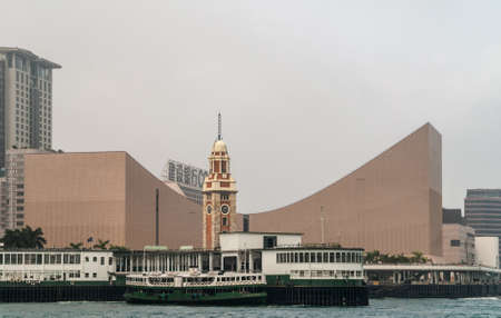 Hong Kong, China  - May 12, 2010: Former Kowloon-Canton Railway Clock Tower in front of Cultural Center and behind ferry docks of Kowloon at Victoria Harbour. Silver sky. Sajtókép