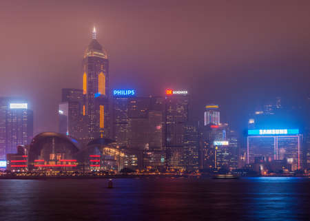 Hong Kong Island, China  - May 12, 2010: Partial night skyline with Convention Center and Central Plaza Tower and more to the west. Lights are on, foggy sky. Editorial