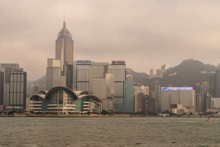 Hong Kong Island, China  - May 12, 2010: Partial skyline with Convention Center and Central Plaza Tower and more to the west. Green hills in back under foggy sky.