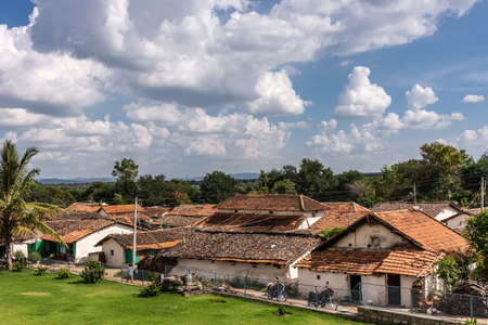 Belavadi, Karnataka, India - November 2, 2013: The red tile roof tops of the small village under blue sky with white clouds. Green vegetation band separates dwellings from sky.