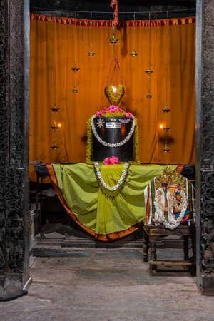 Halebidu, Karnataka, India - November 2, 2013: Hoysaleswara Temple of Shiva. Black stone Shivalingam idol in sanctum against orange backdrop, green dress, flower leis and metal oil lamps. Parvati on chair.