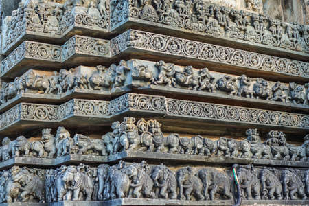 Halebidu, Karnataka, India - November 2, 2013: Hoysaleswara Temple of Shiva. Stack of ribbons of same theme statues on the side of temple building. Gray stone.