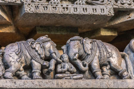 Halebidu, Karnataka, India - November 2, 2013: Hoysaleswara Temple of Shiva. Closeup of statue on side of main sanctuary, where two elephants flank a man in yoga position. Gray brown stone.